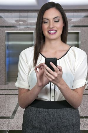texting: A beautiful young woman using a cell phone for texting Stock Photo