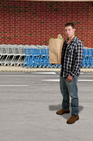 Handsome man grocery shopping holding a brown paper bag photo