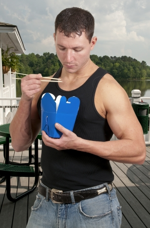 Handsome man eating Chinese Japanese or Asian takeout food photo