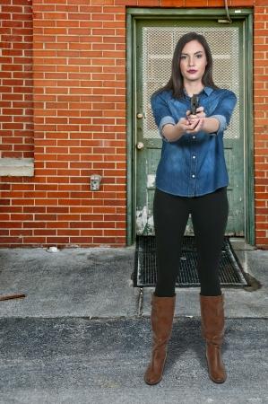 poliziotta: Bella donna detective della polizia sul posto di lavoro con una pistola