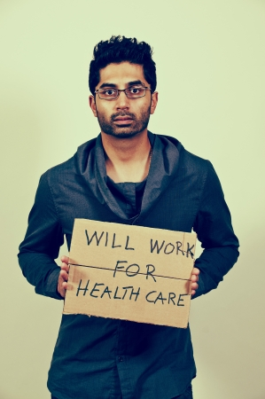 Handsome man holding a sign that says will work for healthcare