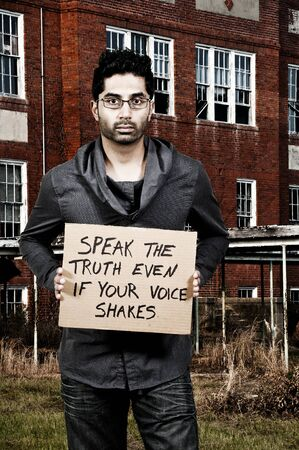 Young man holding up a sign that says Speak The Truth Even If Your Voice Shakes photo