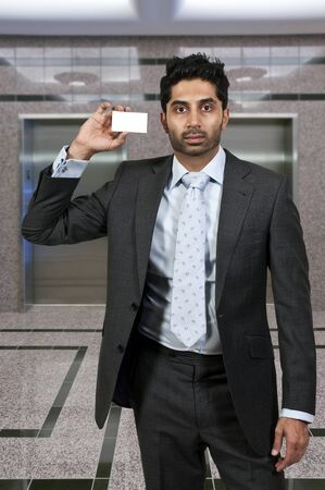 Handsome man holding up a business card Stock Photo - 17426073