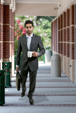 Handsome young man carrying his important papers in a briefcase and coffee photo