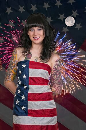 Beautiful woman at a fireworks display wrapped in a flag photo
