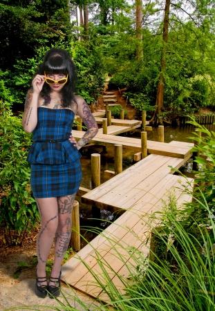 tatt: Woman in sunglassesat a Japanese Zig-Zag Bridge Stock Photo