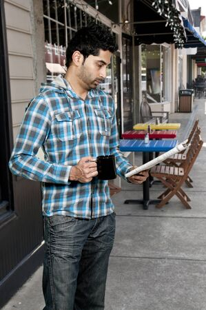 Young handsome man drinking coffee and reading the newspaper in the morning photo