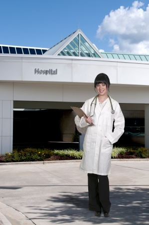 Beautiful young female doctor outside of a hospital photo