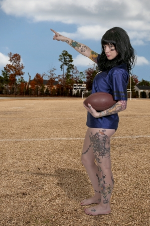 beautiful young woman playing a game of football photo