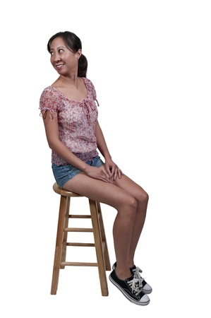 Beautiful young woman stiing on a stool photo