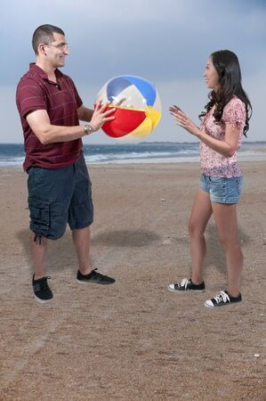 Young couple playing with a beach ball photo