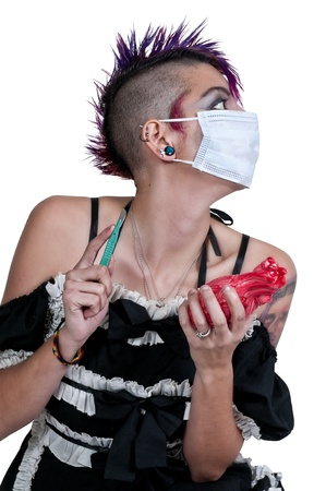 spiked hair: Beautiful gohic woman doing surgery on a heart Stock Photo