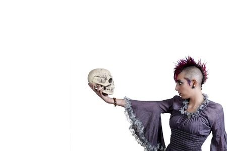 Beautiful young punk rock alternative lifestyle woman holding a skull photo
