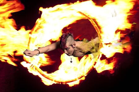 tattoed: Beautiful woman jumping through a ring of fire