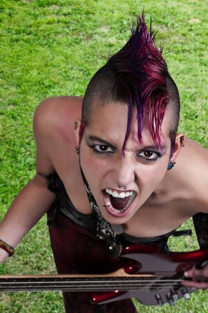 bass guitar women: Beautiful woman punk rocker with an electric bass guitar