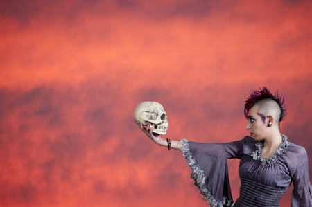 Beautiful young punk rock alternative lifestyle woman holding a skull photo