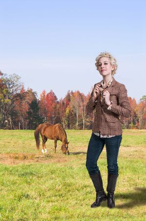 Beautiful woman standing next to a horse photo