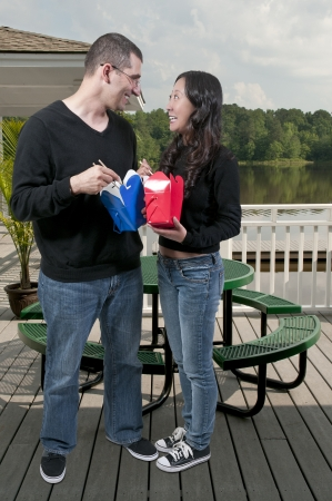 Beautiful woman and handsome man eating Chinese Japanese or Asian takeout food photo