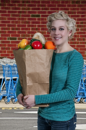 Beautiful woman grocery shopping holding a brown paper bag Stock Photo - 17946486
