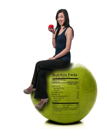 winesap apple: Beautiful young Asian woman sitting on a whole red delicious apple with a nutrition label Stock Photo
