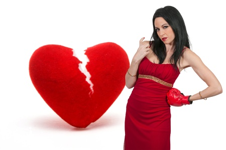 hither: Beautiful woman in wearing a boxing glove in front of a broken heart - heartbreaker Stock Photo