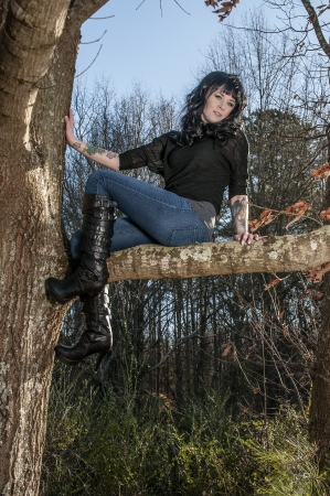 tatt: Beautiful young woman with tattoos sitting in a tree Stock Photo