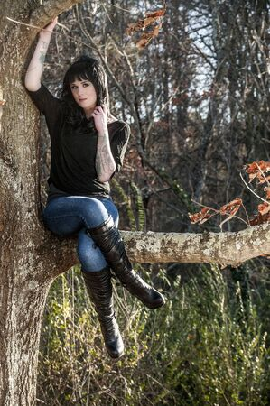 Beautiful young woman with tattoos sitting in a tree photo