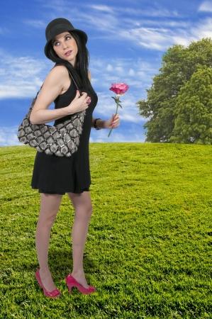 Beautiful woman holding a fresh cut rose photo