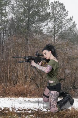 Beautiful young woman holding an automatic assault rifle photo