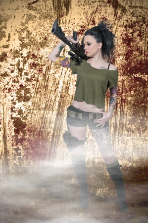 Beautiful young woman holding an automatic assault rifle photo