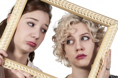Beautiful women looking through an ornate picture frame photo