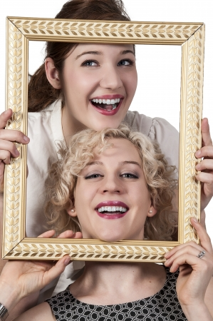 narcissism: Beautiful women looking through an ornate picture frame Stock Photo