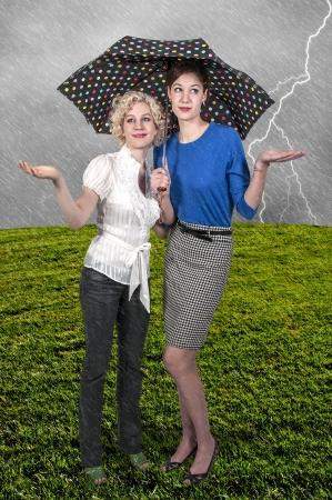 Beautiful young women holding an umbrella in a rain storm photo