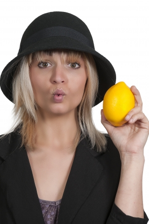 puckering lips: Beautiful woman puckering her lips while holding a lemon Stock Photo