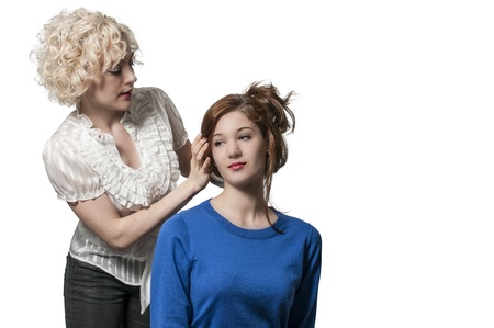 Woman hairstylist working on doing a hair style Фото со стока