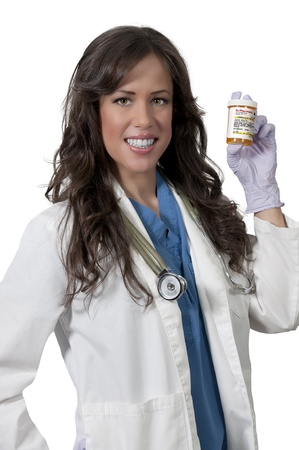 A beautiful young female doctor on her rounds holding a prescription bottle of medicine pills photo