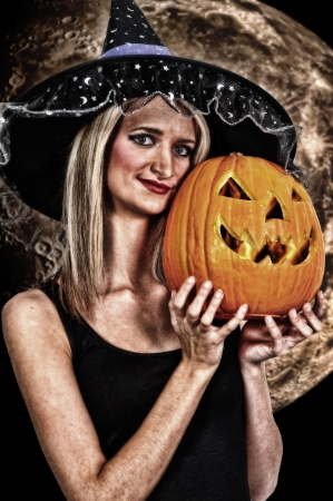 Beautiful woman wicked witch with a pumpkin jack-o-lantern photo