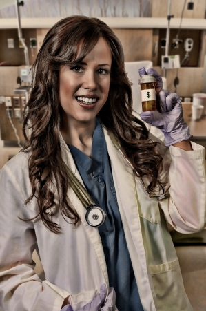 Beautiful young female doctor on her rounds holding a pill bottle of prescription medication photo