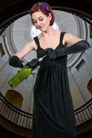 Beautiful woman opening a fine wine bottle