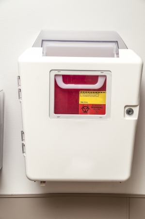 Sharps container on the wal of a patient room in a hospital or doctors office photo