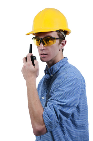 Handsome man construction worker talking on a walkie talkie photo