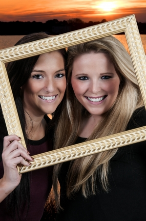 bff: Beautiful women best friends looking through a picture frame at the beach