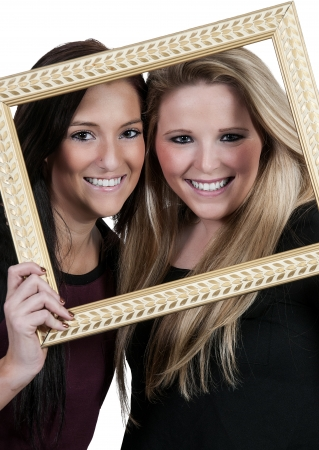 Beautiful women best friends looking through a picture frame photo