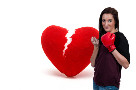 beckon: Beautiful woman in wearing a boxing glove in front of a broken heart - heartbreaker Stock Photo