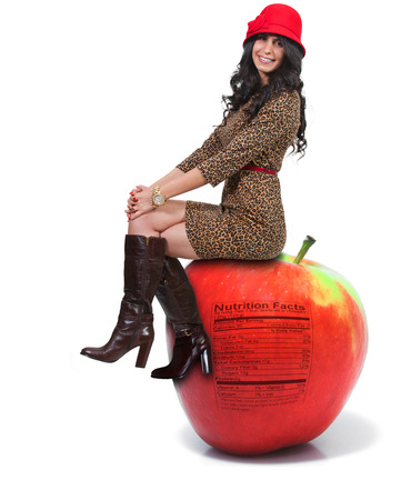 winesap apple: Beautiful young woman sitting on a whole red delicious apple with a nutrition label