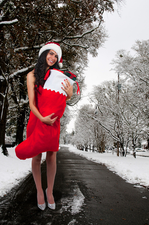 Beautiful woman holding a stocking with Christmas gift presents