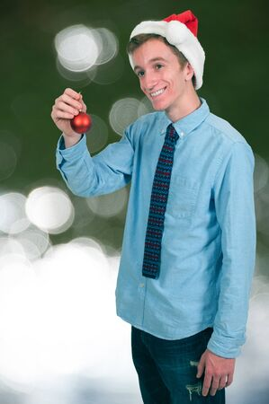Handsome young man holding a Christmas Tree Ornament photo