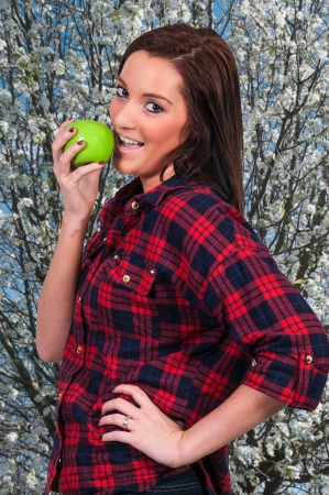 Beautiful young woman eating a fresh delicious apple photo