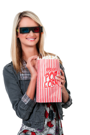 Beautiful young woman watching a 3d movie with popcorn photo