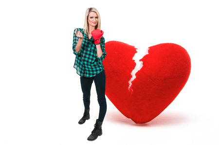 come hither: Beautiful woman in wearing a boxing glove in front of a broken heart - heartbreaker Stock Photo